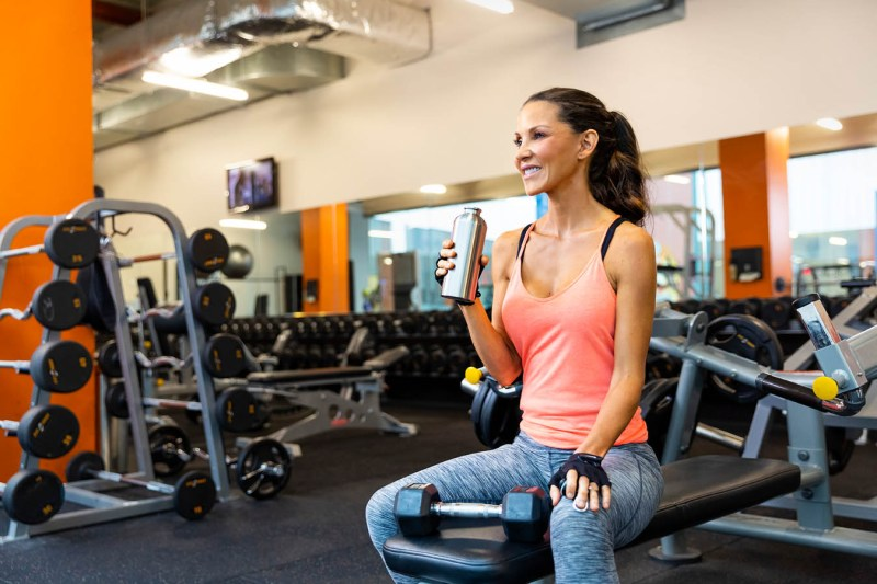 Woman in a gym surrounded by weightlifting equipment holding a water bottle