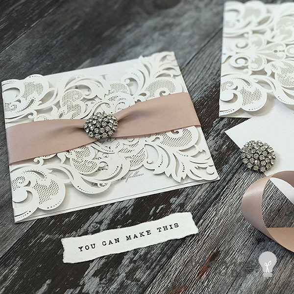 DIY wedding invitations. Nude and white wedding invitations with crystal buckle. Blank laser cut invitation. DIY wedding invitation kit. How to make your own wedding invitations. DIY wedding stationery supplies from Imagine DIY. White laser cut invitation with blush ribbon and crystal buckle.