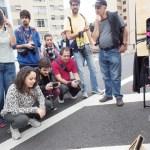 Um grupo de alunos de fotografia que estava passando se interessa pelo processo.