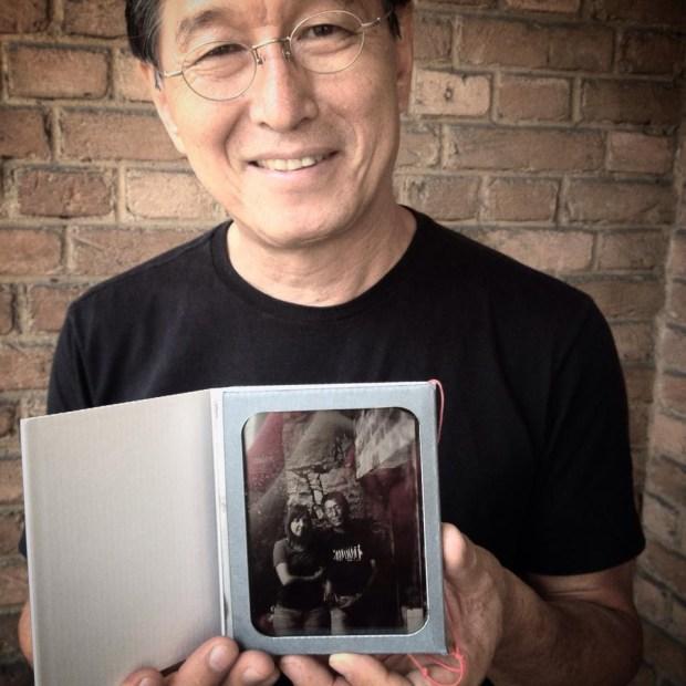 Miguel Chikaoka segurando o retrato em ambrótipo pronto e embalado. Registro de Simone Wicca.