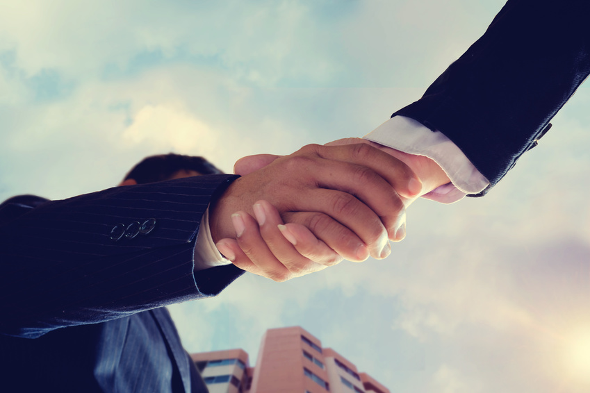 Worm eye view shot of businessmen handshaking.acquisition concept