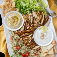 Chicken Shawarma salad platter with tabbouleh, hummus, garlic sauce