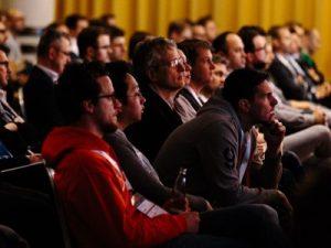 Menschenmenge sitzen nachdenklich, hören gespannt Messensprecher zu