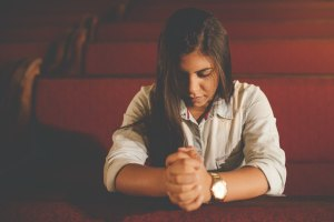 On A Schedule. woman praying wearing a watch. Daily Advent Devotion from Immanuel Lutheran Church in Joplin, Missouri. Call His Name Jesus.