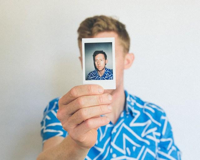 Un homme montrant une photo d'identité qui cache son visage.