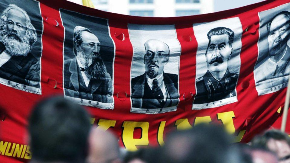 La caduta del muro di Berlino e quello che rimane del comunismo, manifestante con effigi di Lenin, Stalin, Mao e Marx.