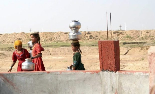 Young girls at a well in Gujarat, which is already facing a water scarcity [image by: Mark Charmer]