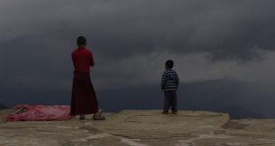 A monk and child stare at an approaching storm at Sanga Choling monastery in Sikkim, India. Should states such as these be compensated for protecting the climate? [image by Andrea Kirkby]