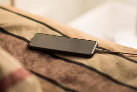 Smartphone charging on a bed
