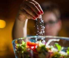 Woman putting salt in a salad