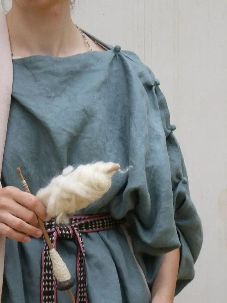 Detalle de una mujer vistiendo un chiton, el cual puede ser identificado por las cuentas en el hombro y las mangas.