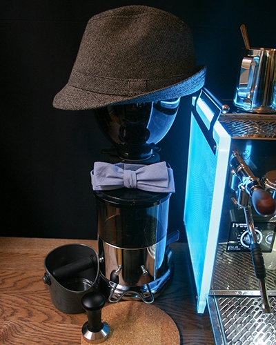 An espresso grinder with a bowtie and a man's hat
