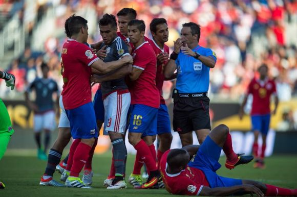 Orlando, Florida - June 04, 2016: Costa Rican defender Johnny Acosta (2) and Costa Rican defender Christian Gamboa (16) try to restrain Paraguayan defender Antonio Sanabria (9) during a Group A Copa America Centenario match between Costa Rica and Paraguay at Camping World Stadium.