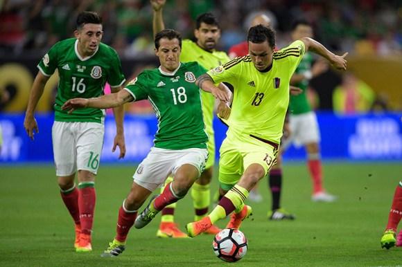 Mexican National Player, Guardado (18) battles against Seijas (13) from Venezuela. Mexico tied Venezuela 1 - 1.