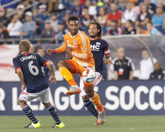 Giles Barnes of Houston Dynamo in the orange jersey goes head-to-head with New England Revolution players in Foxborough, Massachusetts on August 15, 2015.