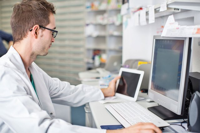 man in lab coat in front of computer terminal comparing information to data on tablet screen