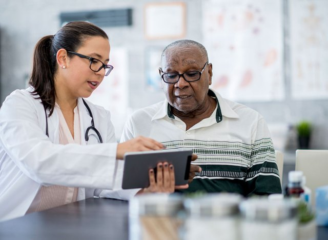 medical professional looking over information on a tablet with a client