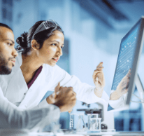 two people in lab coats looking at computer screen