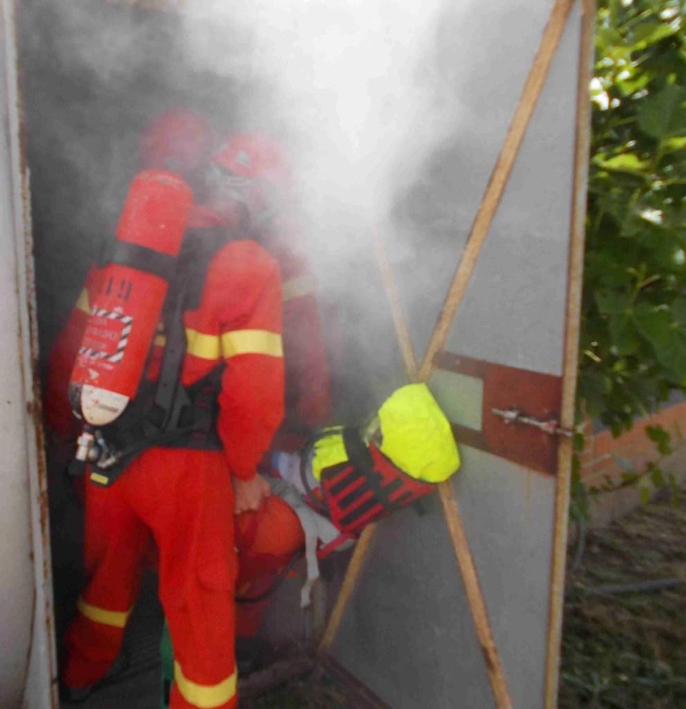 Esercitazione di soccorso e recupero spazi confinati con autorespiratori in camera fumi: due operatori estraggono manichino immobilizzato con collare cervicale e ked
