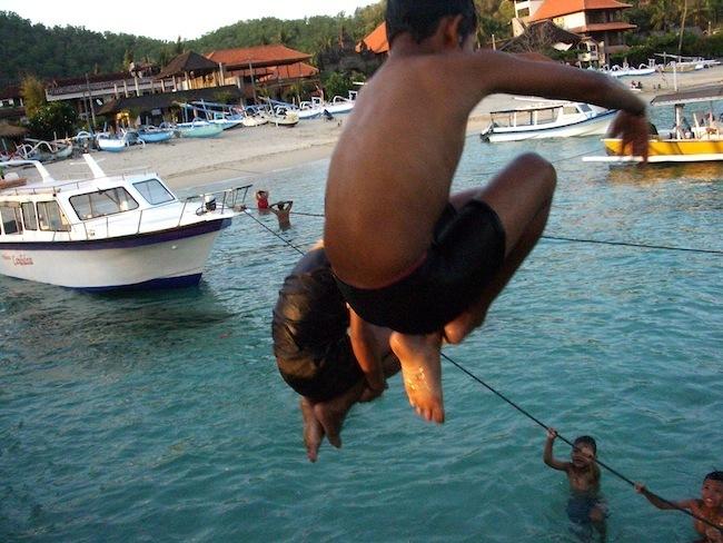 Local children jumping off Padang Bai jetty