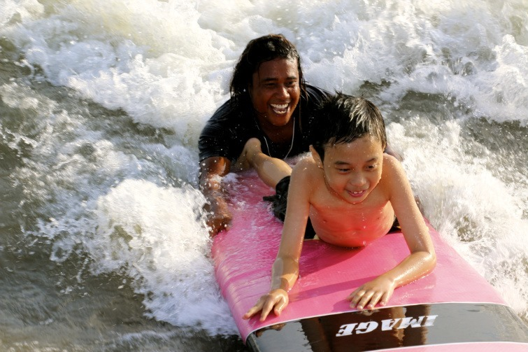 Autisitic boy and his teacher both smiling and riding a surfboard