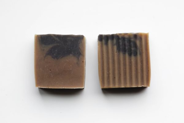 2 brown soaps next to one another with a black swirl on top of each one
