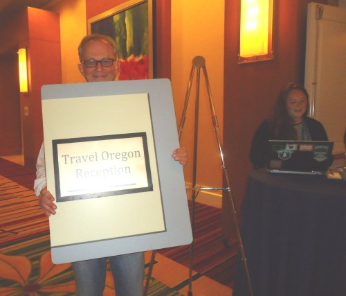 Jake Steinman, founder and CEO of the NAJ Group, attempts to purloin the signage directing delegates to the Travel Oregon party.