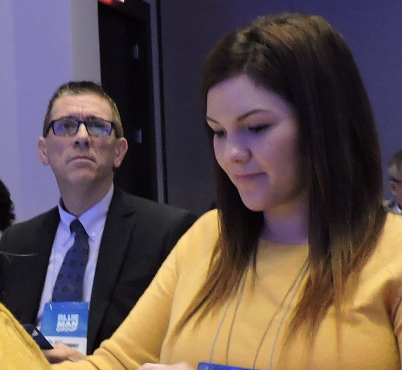 Each following the action in his or her own way: Magan Adams (right), sales manager at The Court of Two Sisters in New Orleans; and Mike Prejean, supervisor in the Louisiana Office of Tourism.