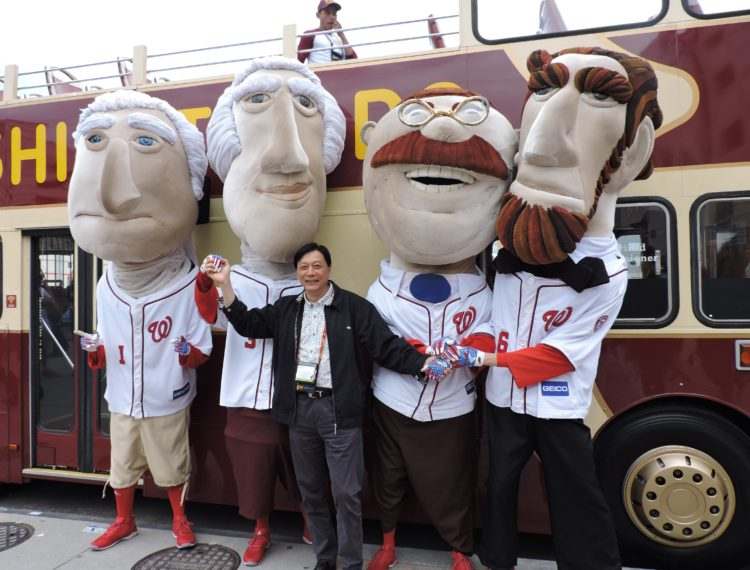 Ding Hai Yang, vice president of the Suzhou Tourism Union in China, is surrounded by the U.S. Presidential mascots for the Washington Nationals baseball team.