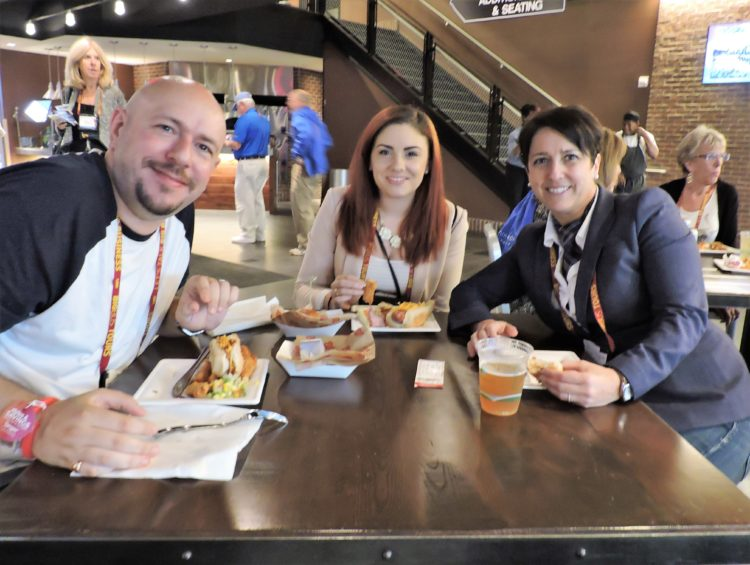 Enjoying the ballpark food (left to right): Jonathan Elkoubi, director-tourism, group sales and corporate events, Appleee's; Stephanie Peed, group sales manager, Applbee's Mid-Atlantic; and Carolina Data, director of sales and special events, Original Joe's (of San Francisco).