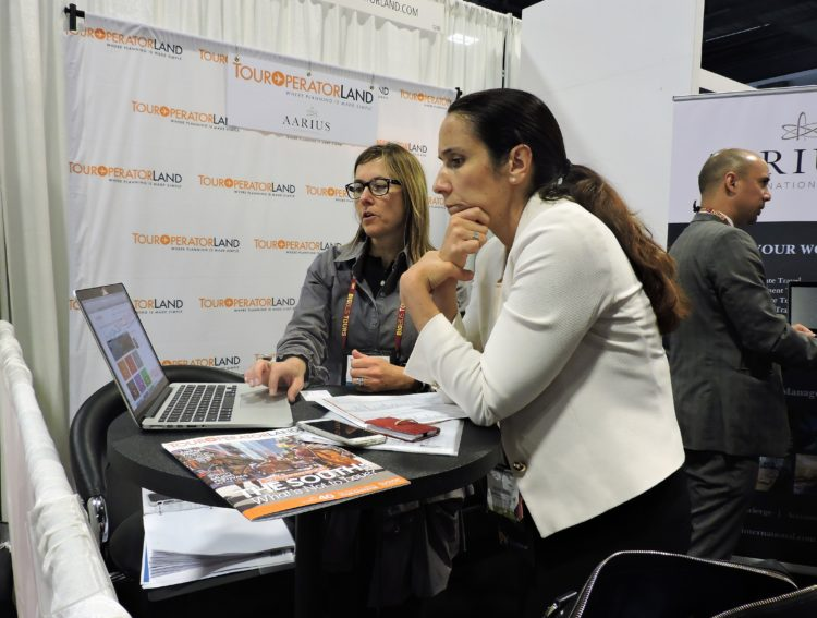 Betsy Cooper (left), tour operator community manager/marketing, NAJ Group, shows Audrey Poirot, regional product director at Destinations of the World, how to build an itinerary and find photos for brochures at TourOperatorLand.com, website of the NAJ Group, which publishes the Inbound Report.