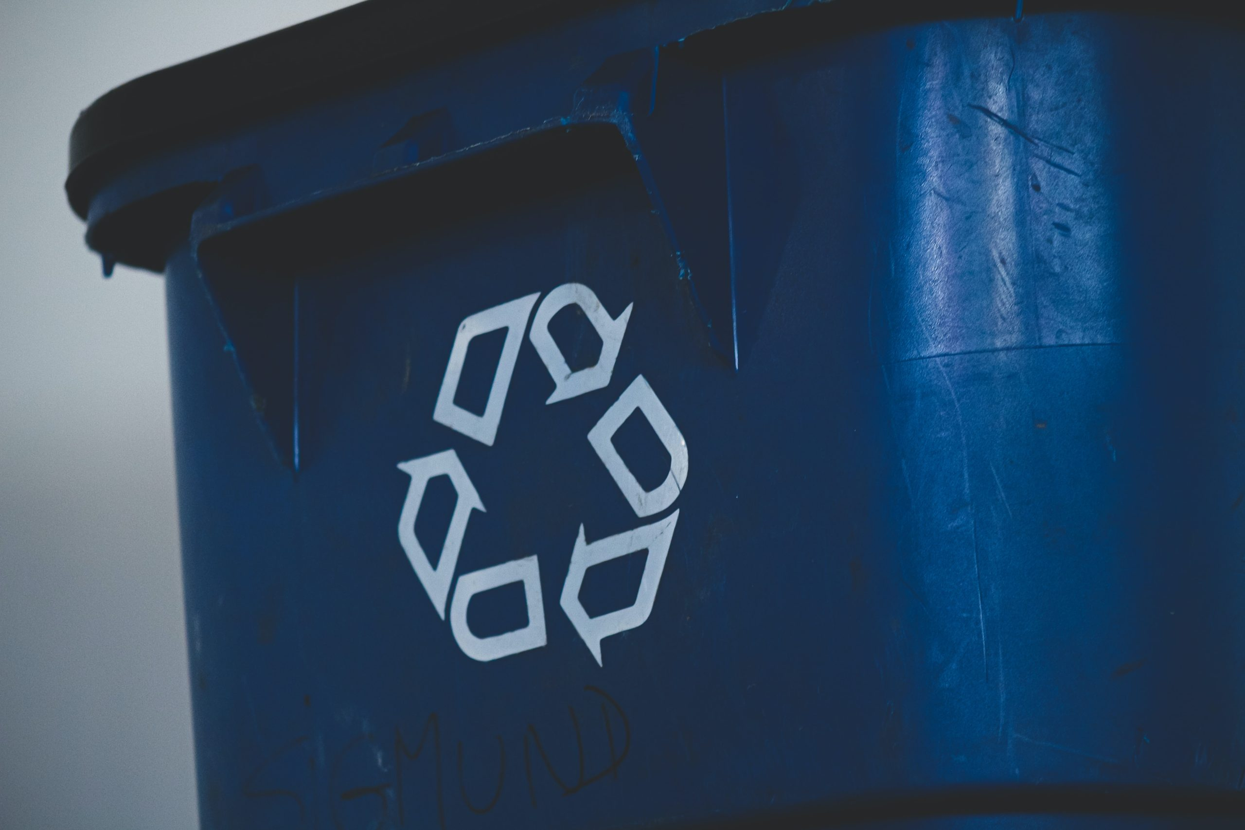 Reuse Recycle symbol on blue bin for people to be less wasteful