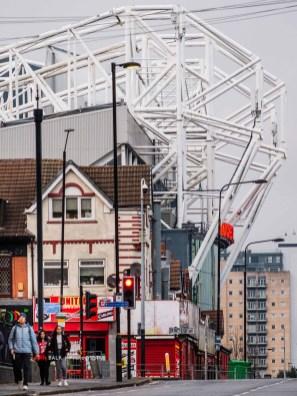 Ook in Engeland zie je steeds minder, de grote oude stadions zijn vrijwel verdwenen uit de steden. Old Trafford ligt tussen een woonwijk en het oude industriegebied in het westen van Manchester. Het stadion staat er al sinds 1910, maar is inmiddels al ontelbare keren verbouwd en vooral uitgebouwd. Een telelens vertekend, zo lijkt de tribune nog groter en dichter op de huizen te staan, maar in het echt zit er nog een spoorlijn tussen.