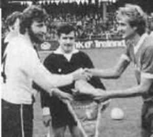Dermot Keely exchanges pennants with Liverpool captain Phil Thompson before a European Cup tie at Oriel Park in 1982