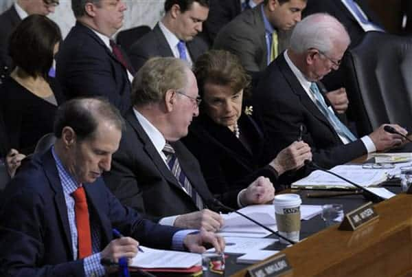 Senate Intelligence Committee Chair Sen. Dianne Feinstein, D-Calif., center, talks with Sen. John D. Rockefeller, D-W.Va., on Capitol Hill in Washington, Tuesday, March 12, 2013, during the committee's hearing on worldwide threats. From left are, Sen. Ron Wyden, D-Ore., Rockefeller, Feinstein, and committee Vice Chairman Sen. Saxby Chambliss, R-Ga. (AP Photo/Susan Walsh)