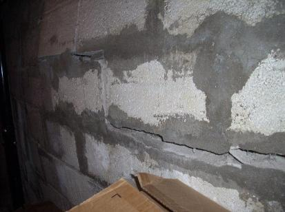 bowing and cracking cinderblock wall with old patchwork