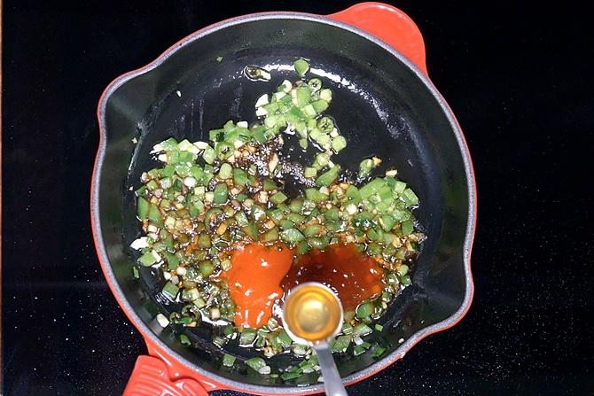 adding sauces and vinegar to make gobi manchurian