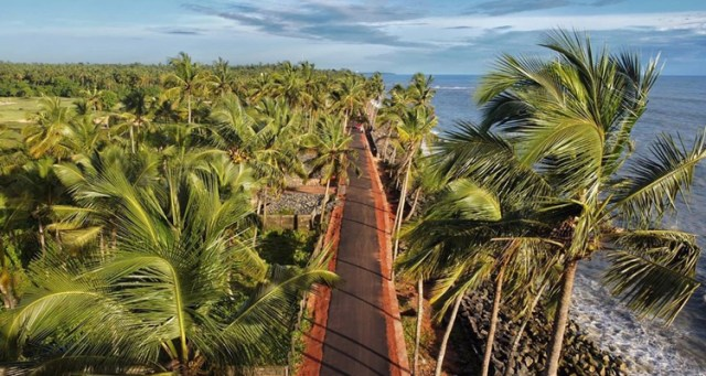 A stunning view of Kappad beach in Calicut, Kerala with coconut trees on the other side of the beach.