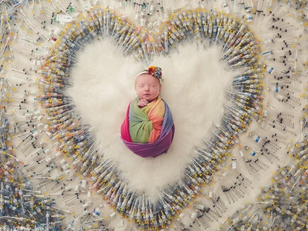 The image is that of a newborn surrounded by syringes arranged in the shape of a heart. The photo, which was posted on social media on August 11, has been melting hearts of people ever since.