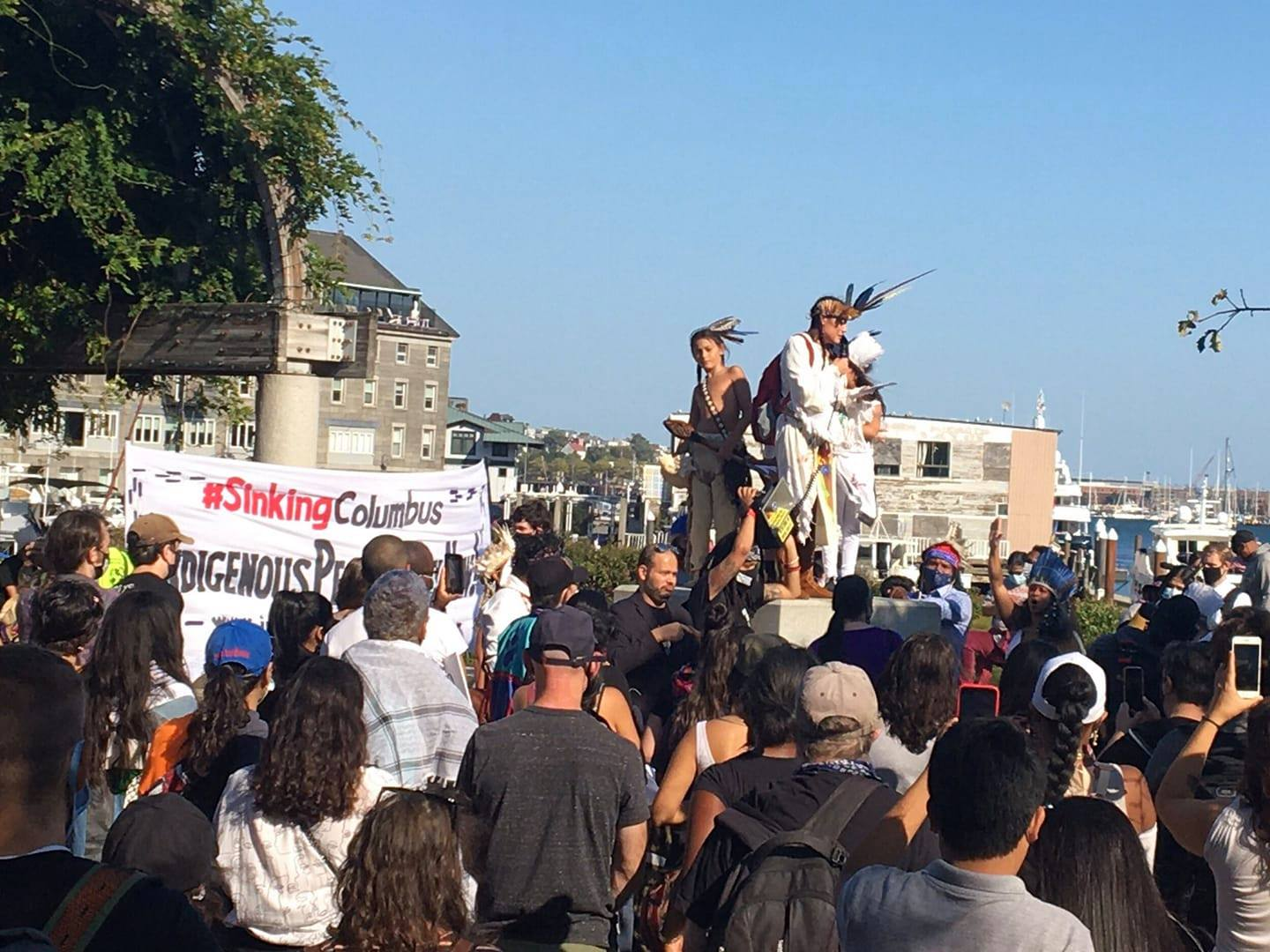Chali'Naru Dones, Taíno, speaking to a crowd from on top of the column that formerly held the Columbus Day Statue in Boston