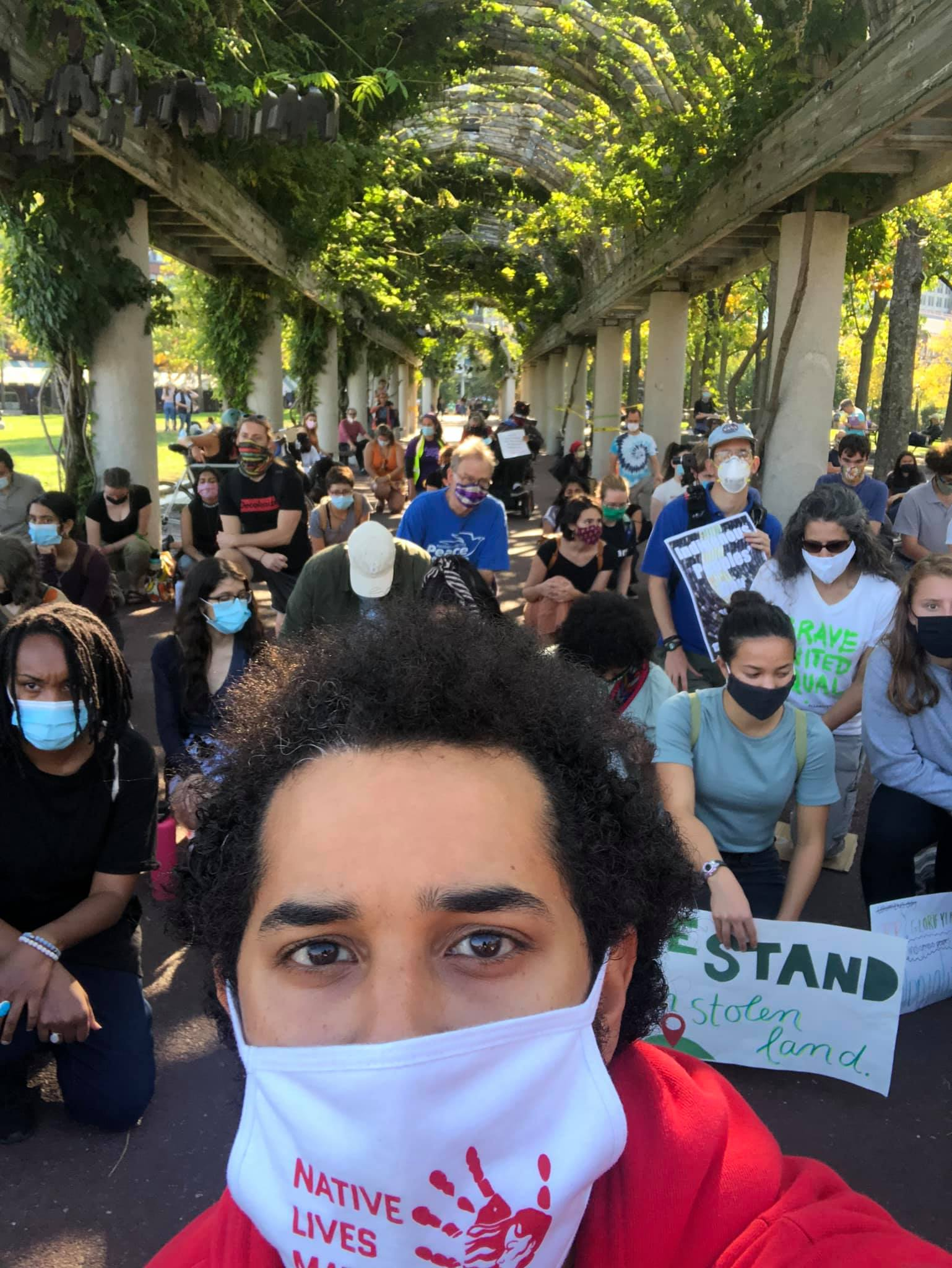 "Selfie taken at Indigenous Peoples Day march in Boston's Columbus Park. Photo taker has mask that reads ""Native Lives Matter"". Many people in march are in view behind"