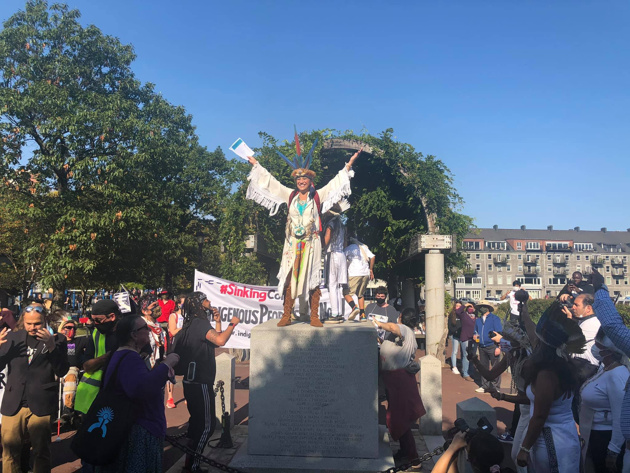 Chali'Naru Dones, Taíno, speaking with arms outstretched to a crowd from on top of the column that formerly held the Columbus Day Statue in Boston