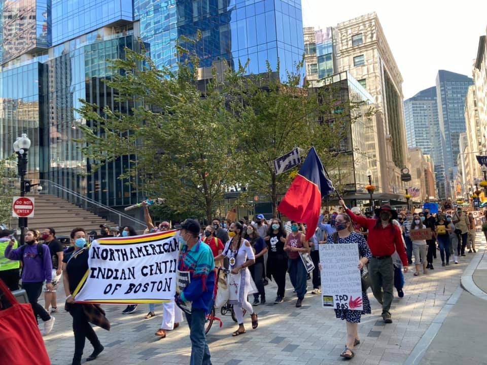 "Indigenous Peoples Day March moving through downtown Boston. People are holding a banner that reads ""North American Indian Center of Boston"""