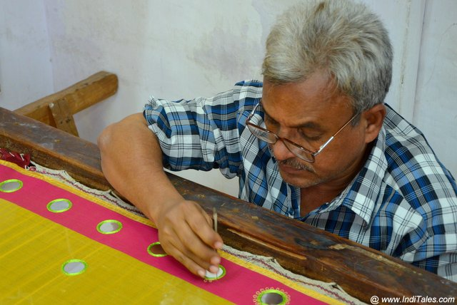 Artisans decorating standing scarves