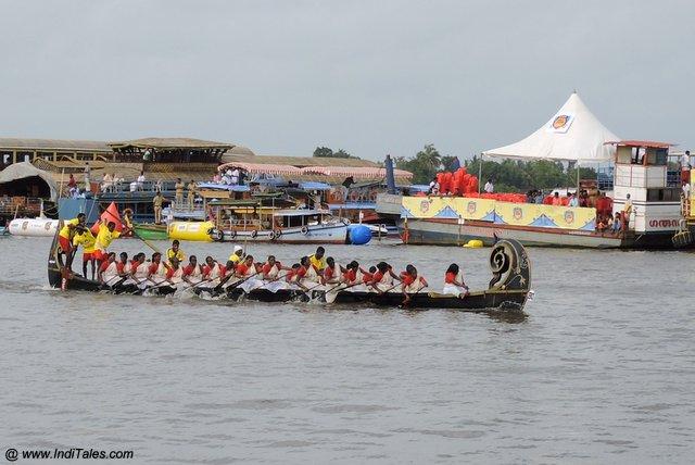 साडी पहने महिलाएं नौका दौड़ में