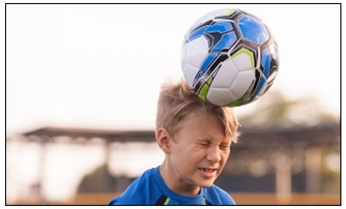 hildren heading ball while playing football