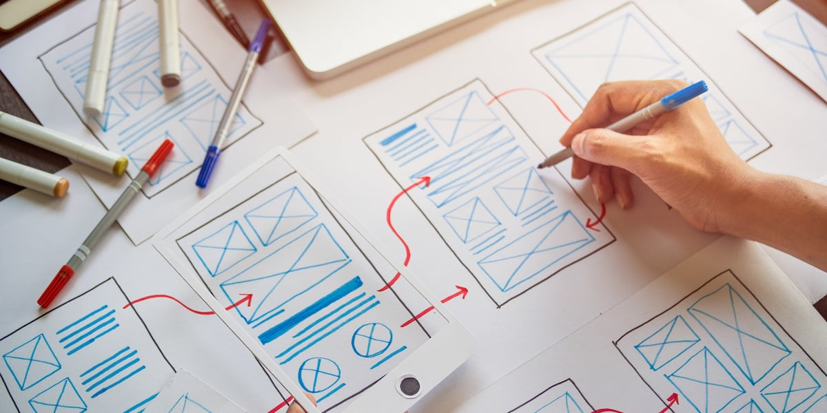 A UX designer connecting paper wireframes into a user flow