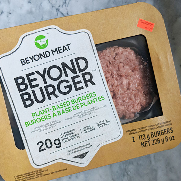 Plant=based burger patty wrapped in a conventional meat patty packaging.