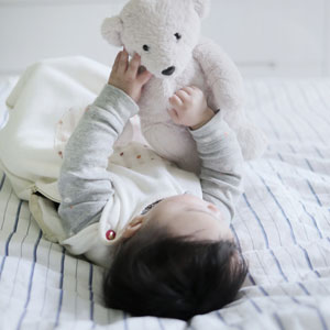 Baby playing with a bear on the bed sleeping through the night.