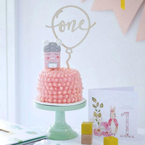 naturally pink smash cake on a green cake stand